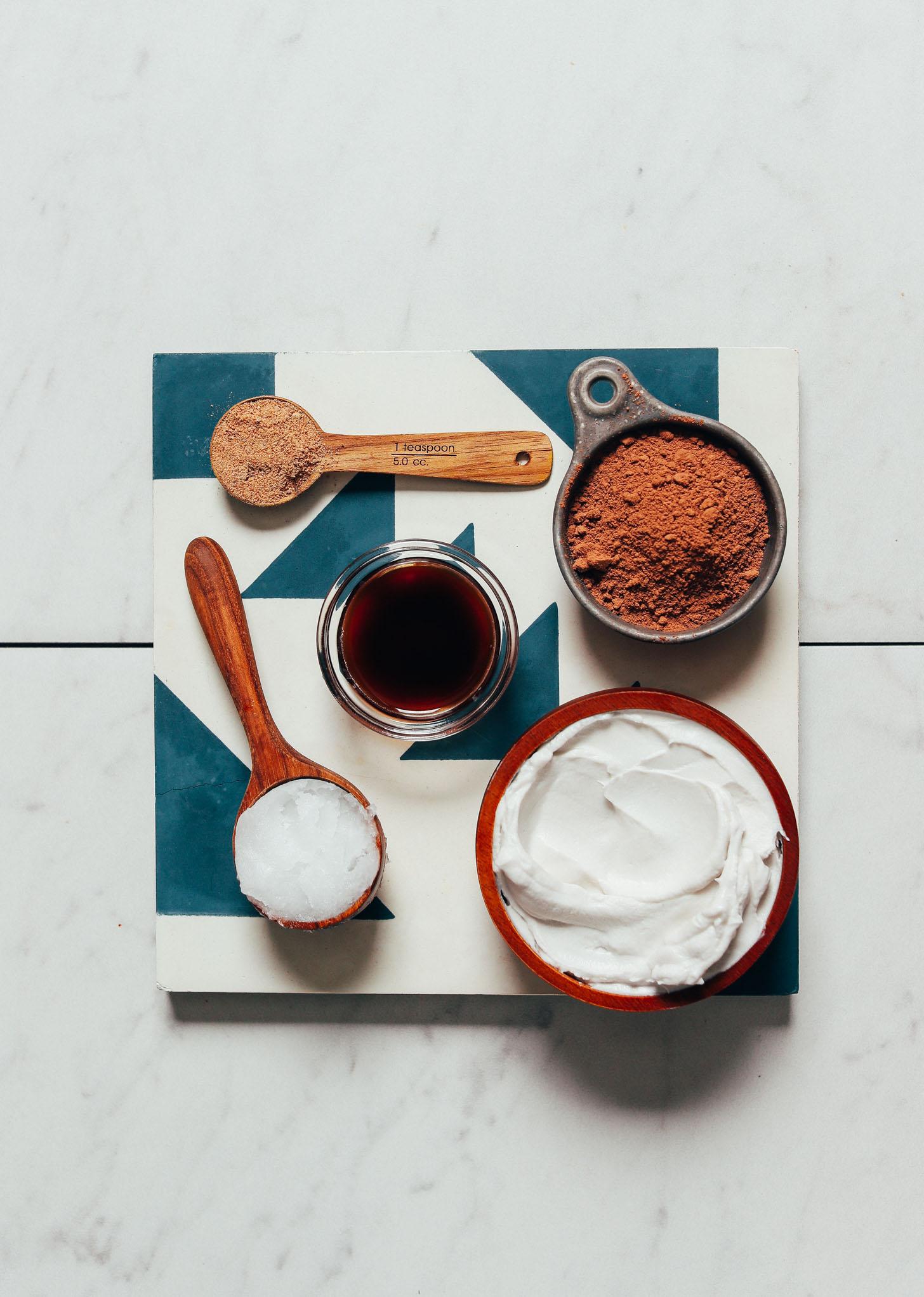 Kokoscreme, Kakaopulver, Kokosöl und andere Zutaten für unser hausgemachtes veganes Milchschokoladenrezept