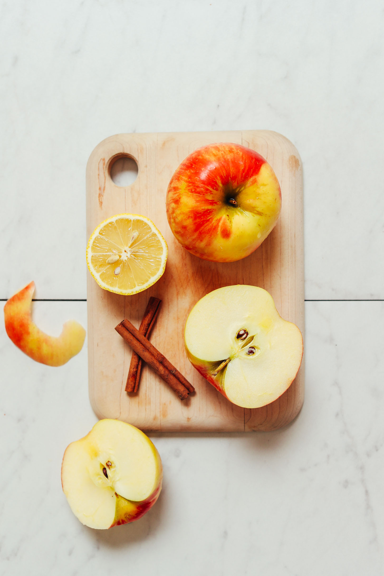 Cutting board with apples, lemon, and cinnamon sticks