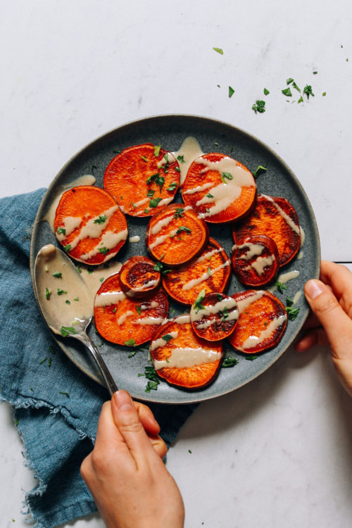 Plate of quick and easy sweet potatoes drizzled with tahini