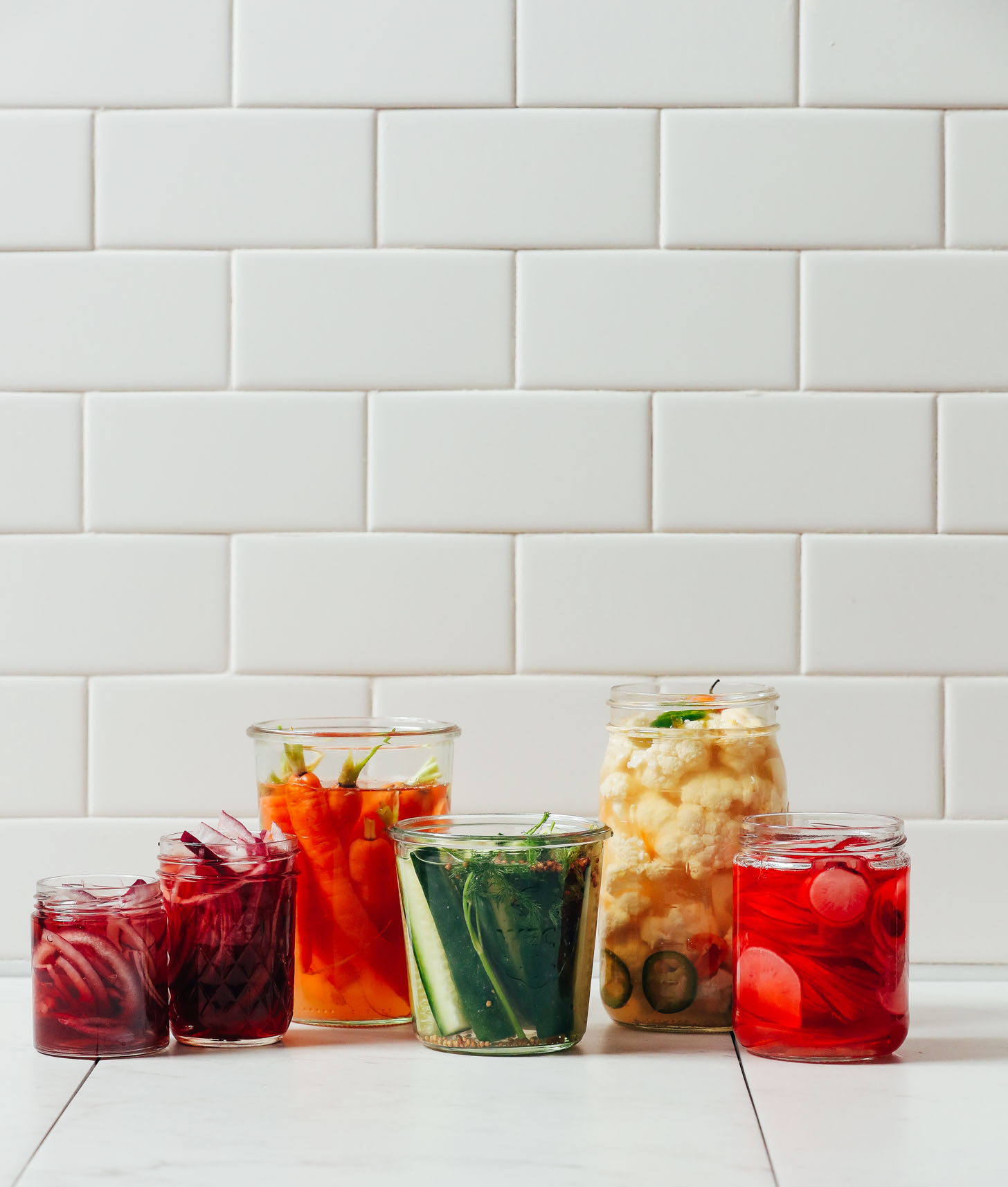 Jars of quickly pickled vegetables, including onions, carrots, cucumbers, cauliflower, and radishes