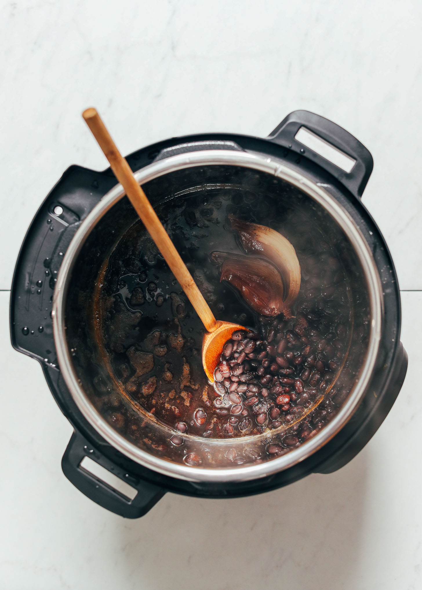 Wooden spoon in a pot of perfectly cooked easy Instant Pot Black Beans