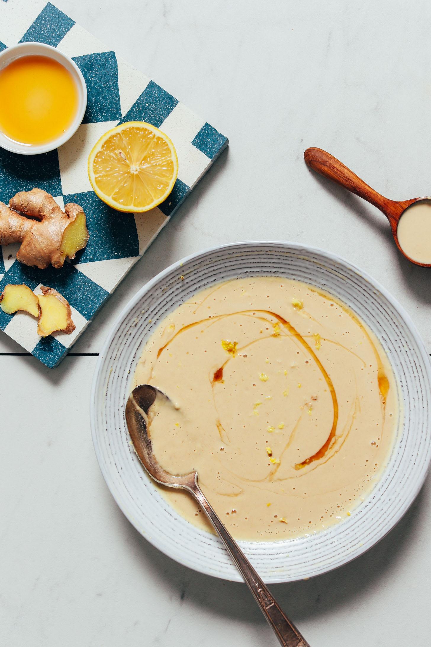 Mitad de limón, jengibre en rodajas, jarabe de arce y tahini junto a un plato de nuestra receta de salsa de jengibre y tahini de limón