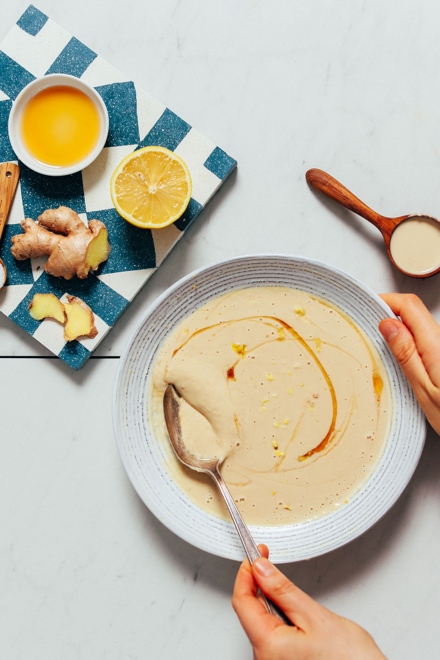 La ralladura de limón y un remolino de jarabe de arce en un tazón de nuestra salsa de jengibre Tahini de limón