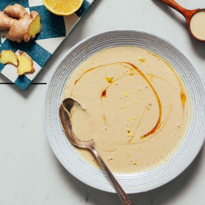 Spoon resting in a bowl of our Lemony Ginger Tahini Sauce