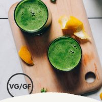 Two glasses of our Easy Green Juice recipe on a cutting board beside ingredients used to make it