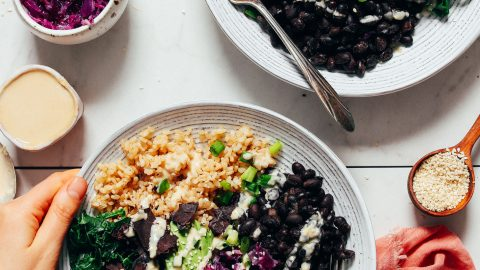 Holding the side of a Black Bean Buddha Bowl with Lemon Ginger Tahini Dressing