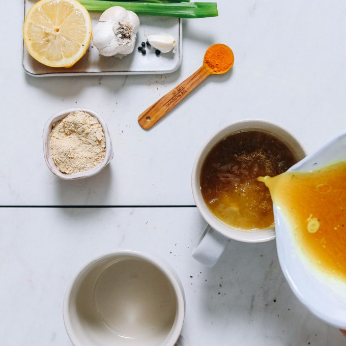 Pouring chicken broth into a mug to make our Bone Broth Tonic recipe