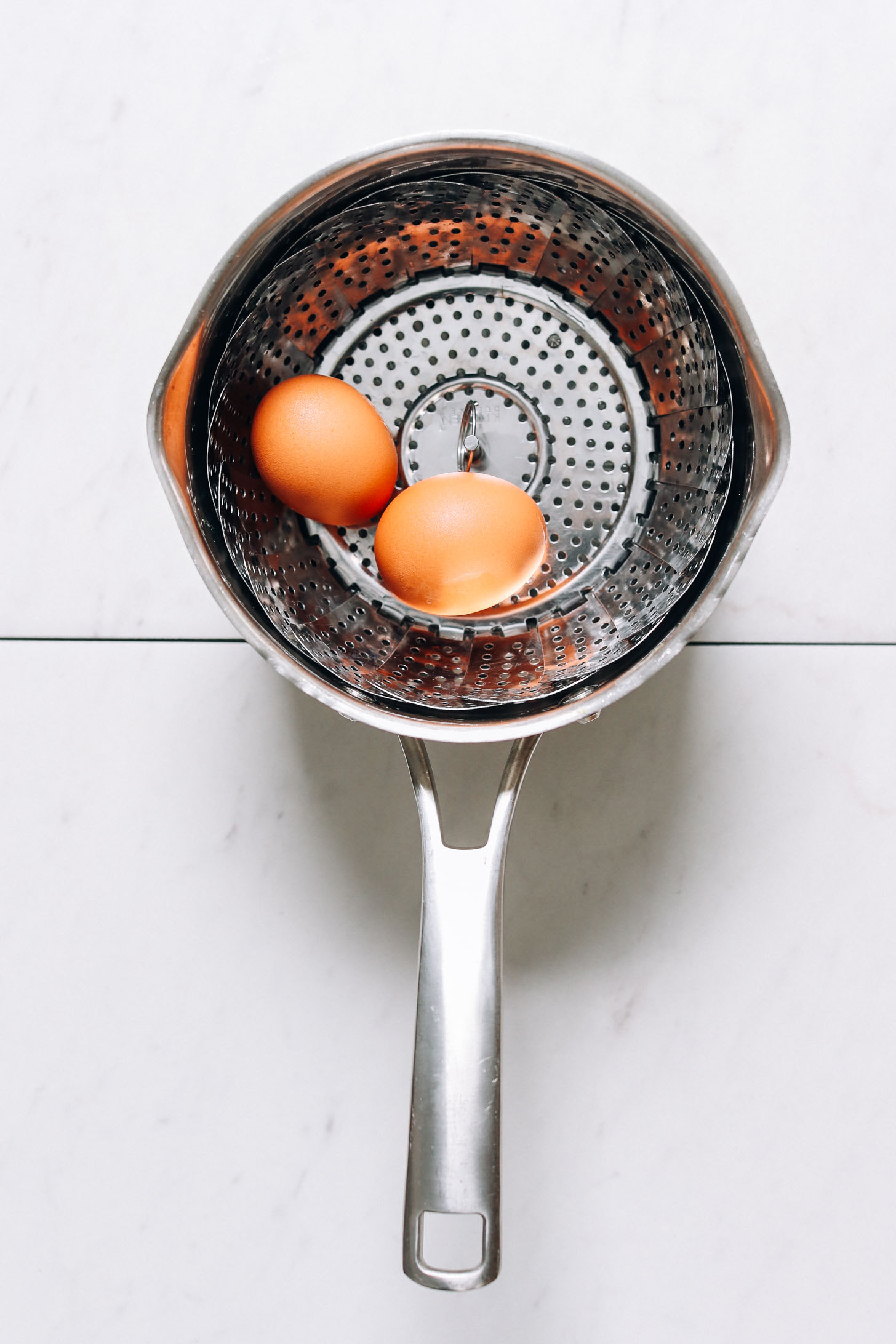 Eggs in a steamer basket to show how to steam hard boiled eggs