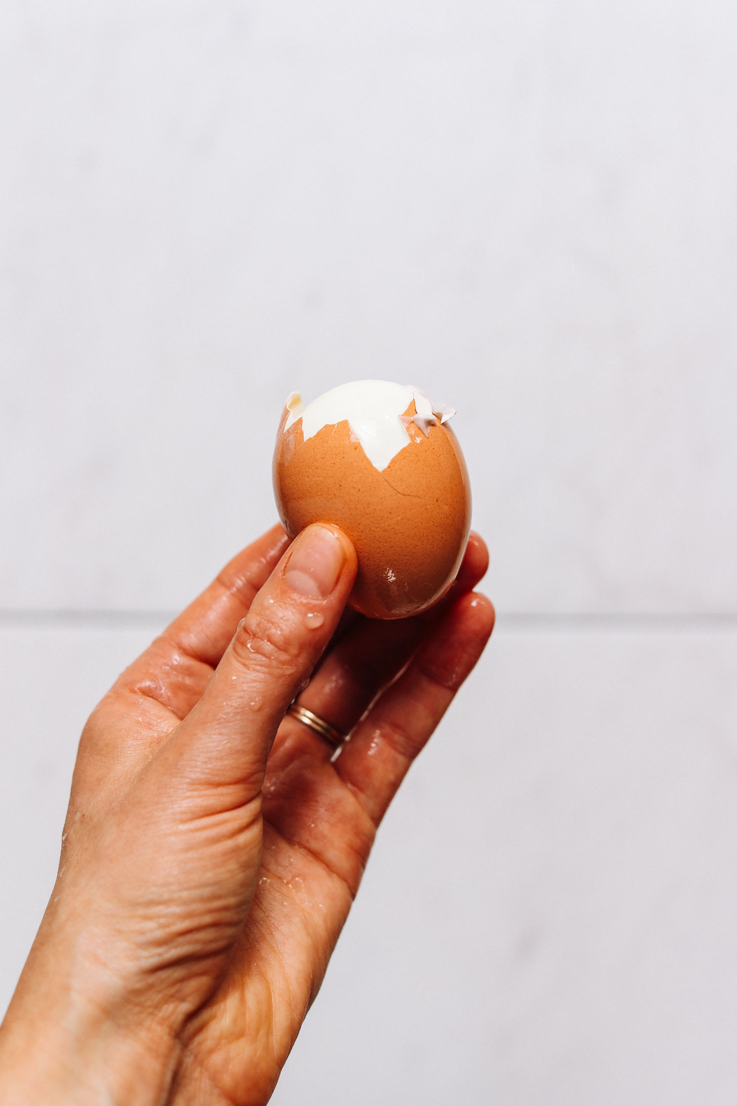 Showing a partially peeled hard boiled egg