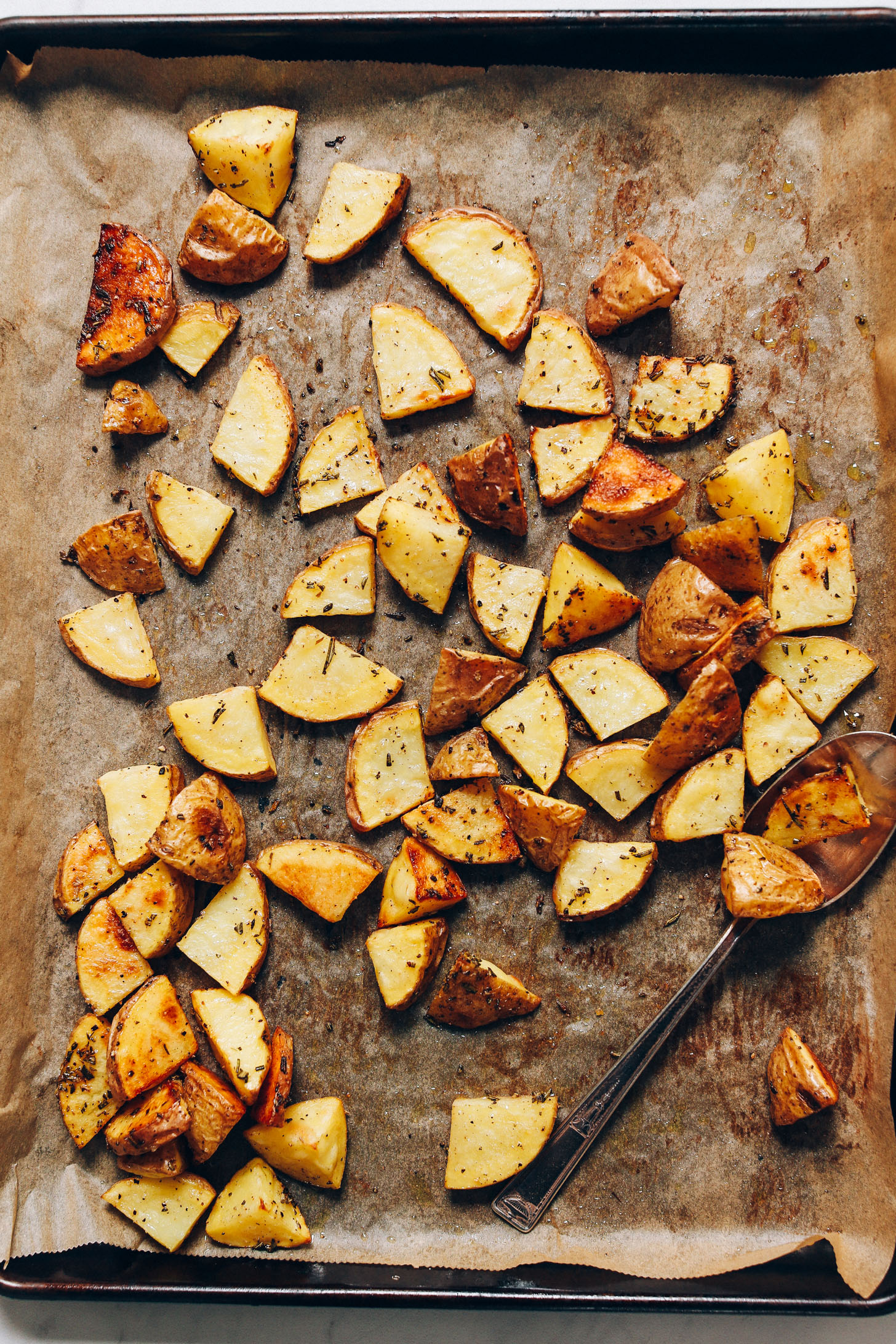 Parchment-lined baking sheet filled with Crispy Oven Roasted Potatoes