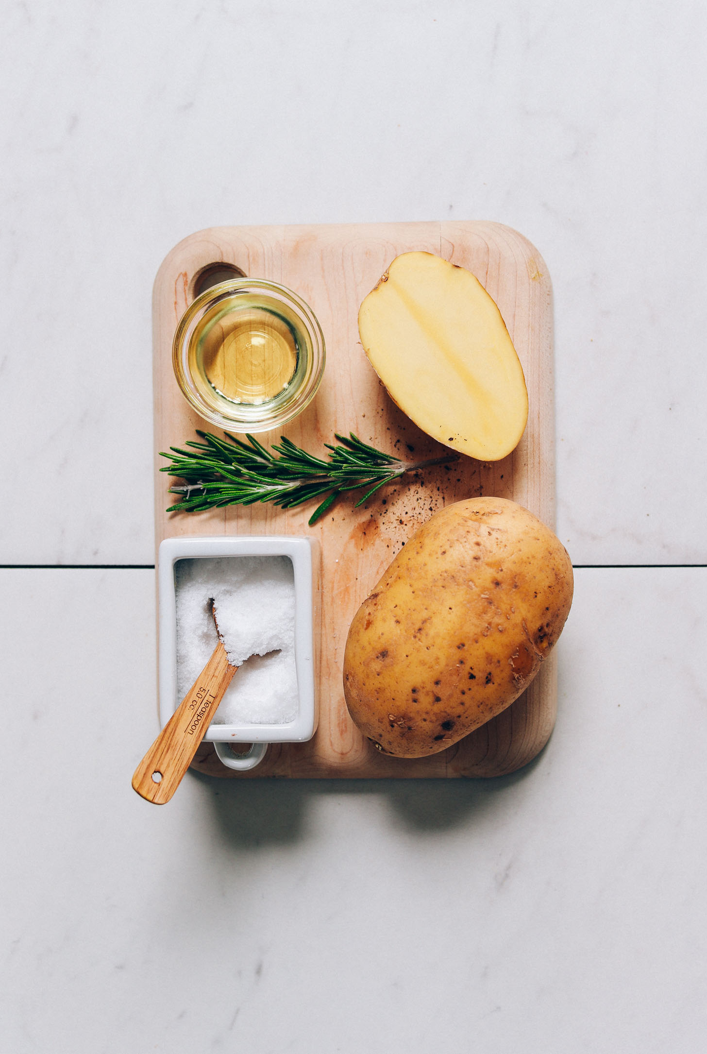 Small cutting board with gold potatoes, avocado oil, rosemary, and salt for making Oven Roasted Potatoes