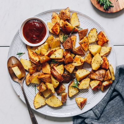 Spoon resting on a plate of Roasted Potatoes with a bowl of ketchup