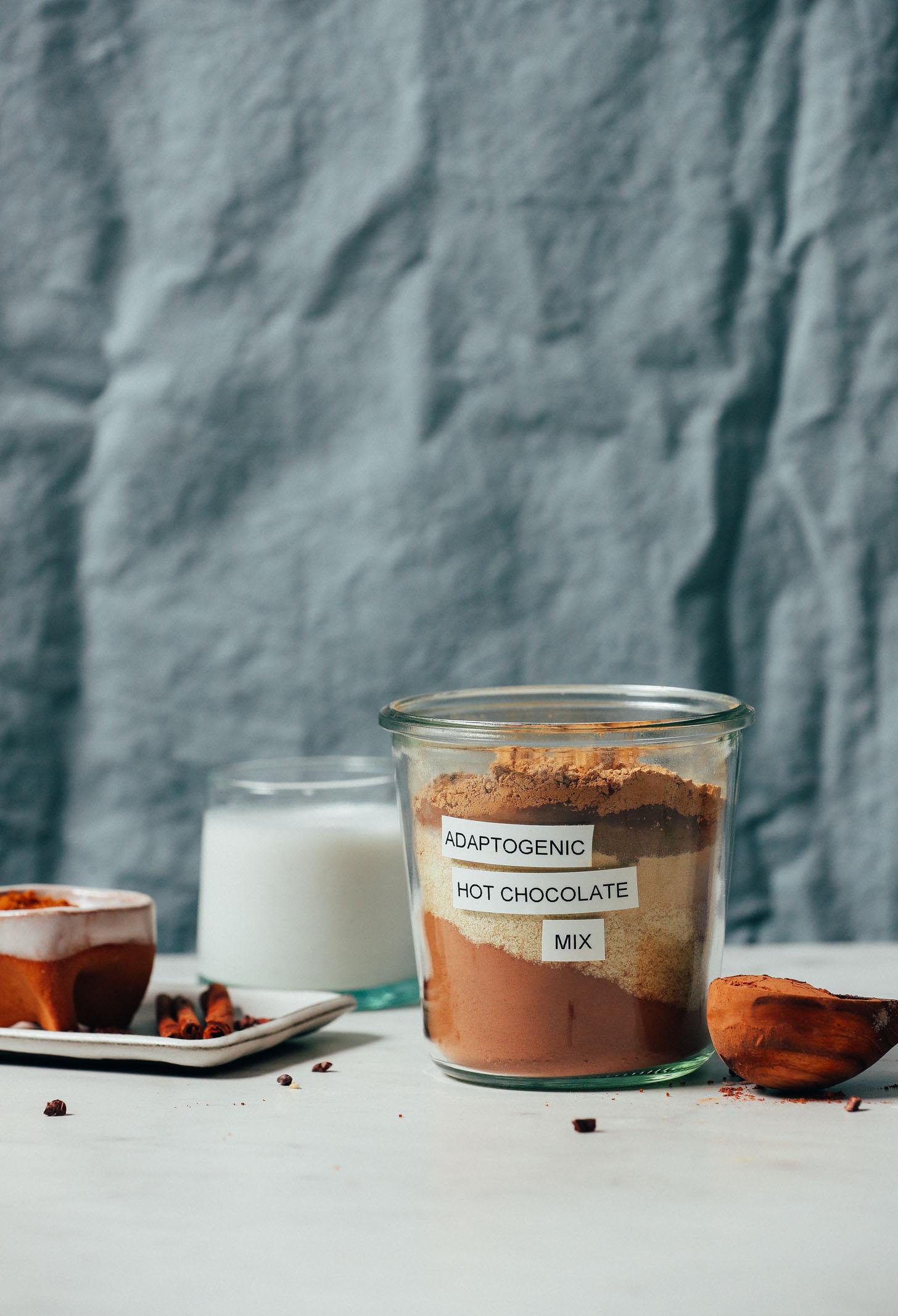 Palitos de canela, cacao en polvo, leche de almendras y azúcar de coco junto a un frasco de mezcla adaptogénica de chocolate caliente