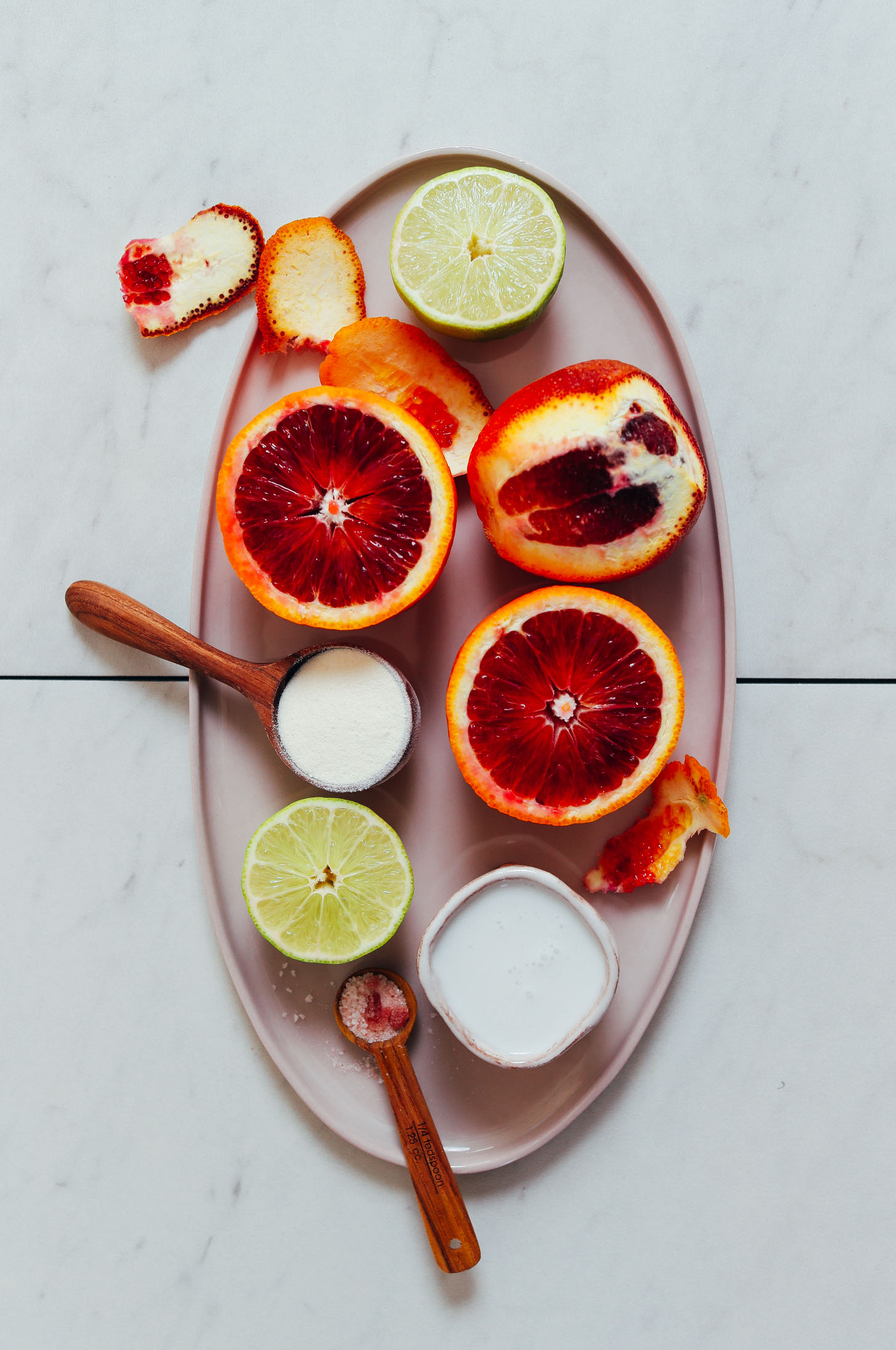 Platter of limes, blood oranges, coconut milk, collagen, and pink salt for making our Creamsicle Smoothie recipe