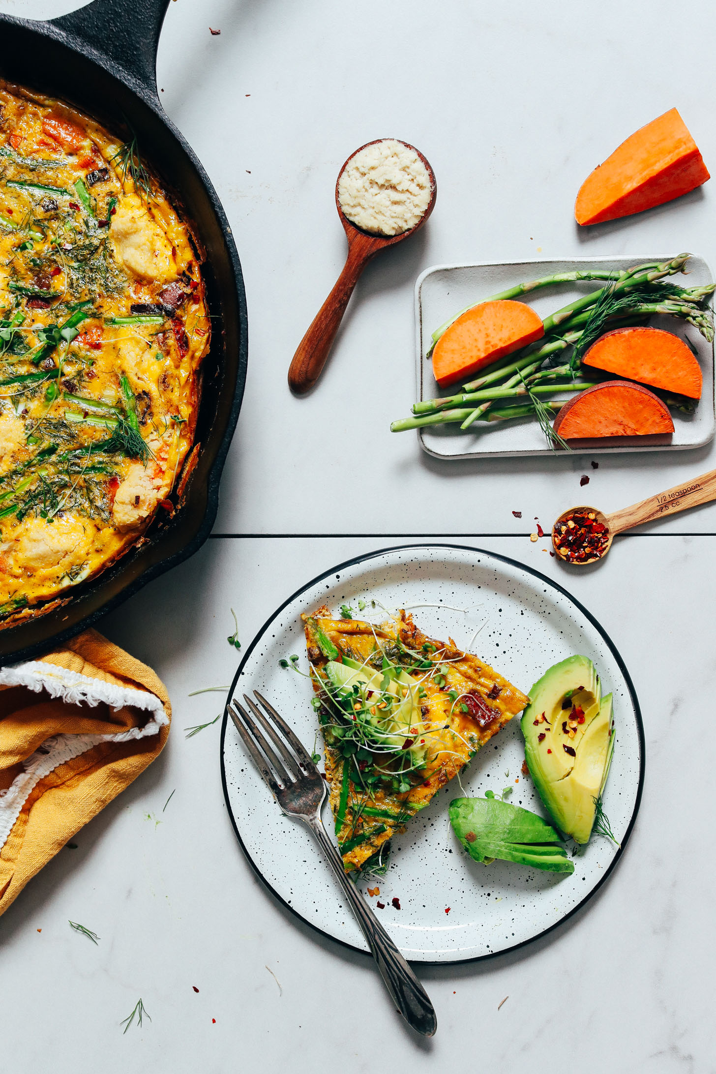 Skillet and slice of our Spring Vegetable Frittata with the slice topped with avocado, red pepper flake, and microgreens