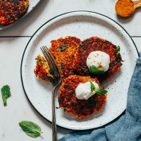 Slicing into Sweet Potato Quinoa Fritters on a plate