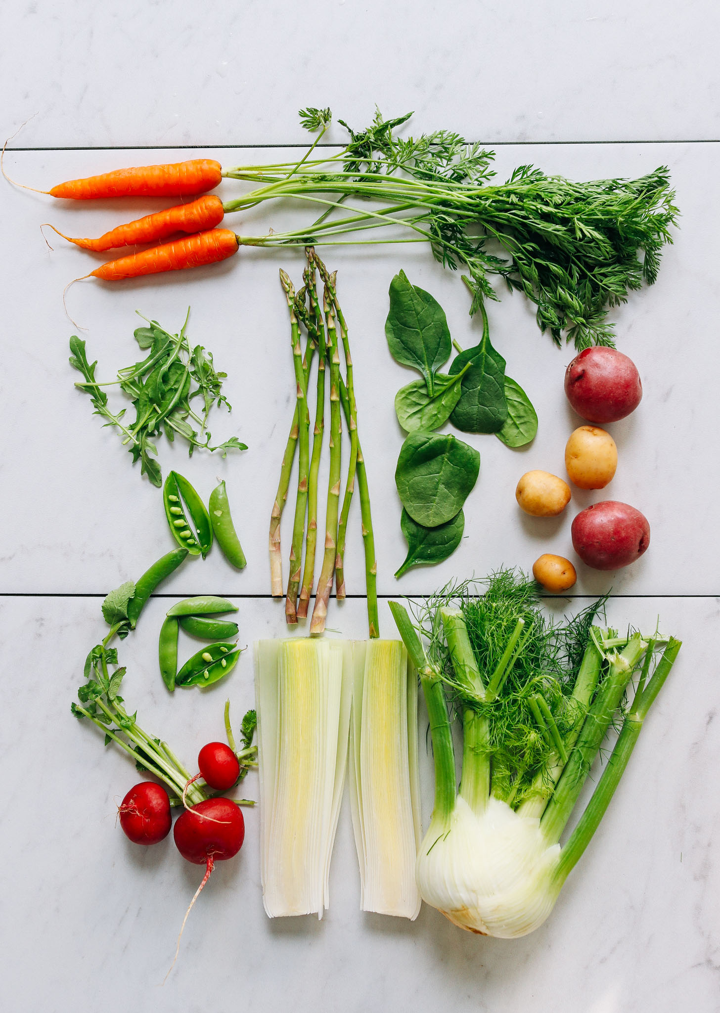Assortment of spring vegetables including carrots, asparagus, spinach, potatoes, and more