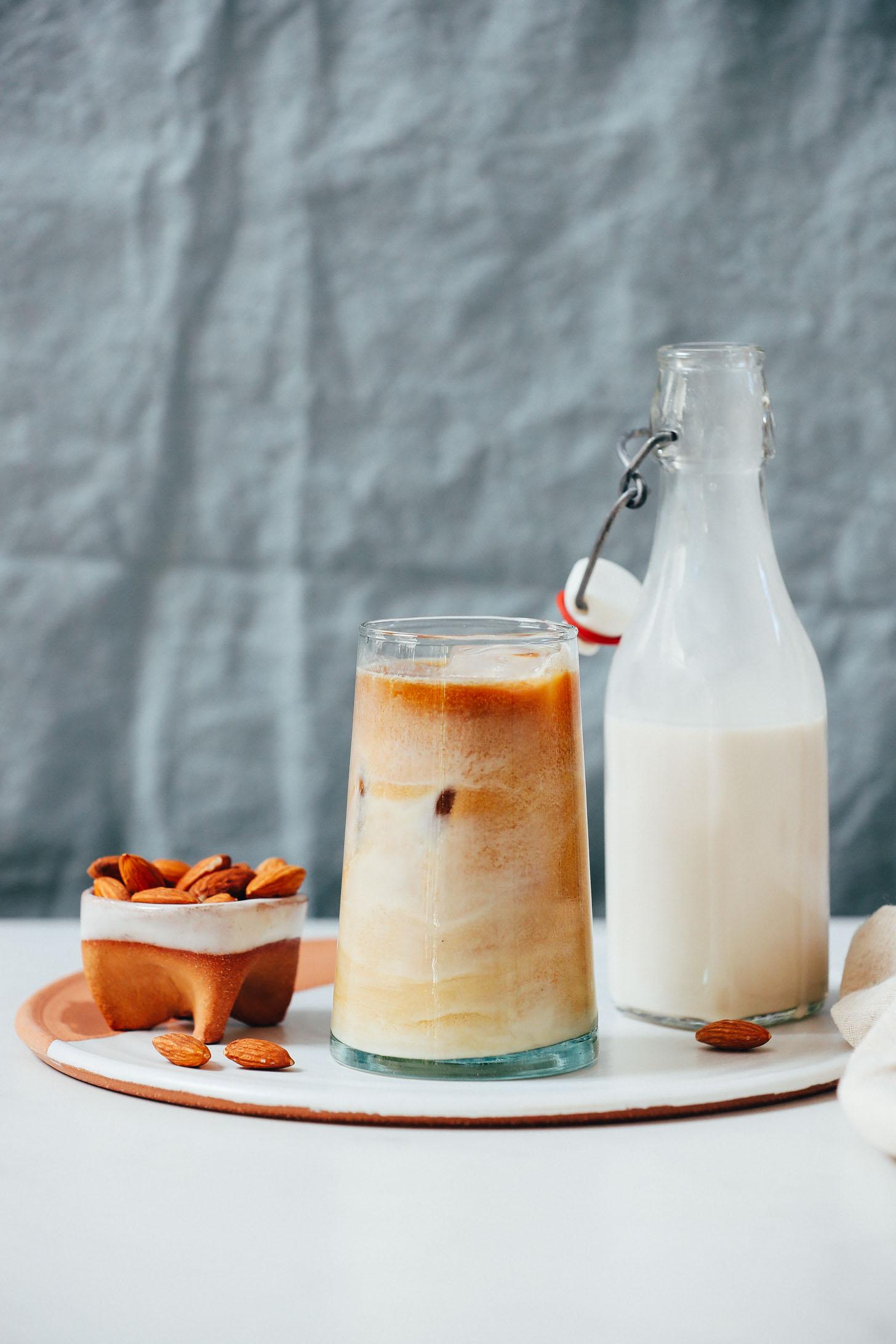 Tigela de amêndoas ao lado de um café gelado e recipiente de creme de leite com amêndoa