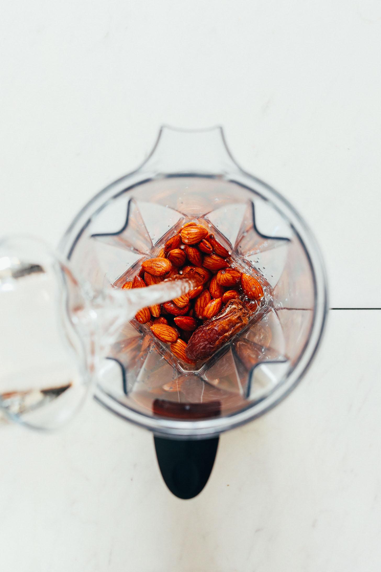Agregar agua a una licuadora llena de almendras para nuestra receta de crema de café hecha en casa