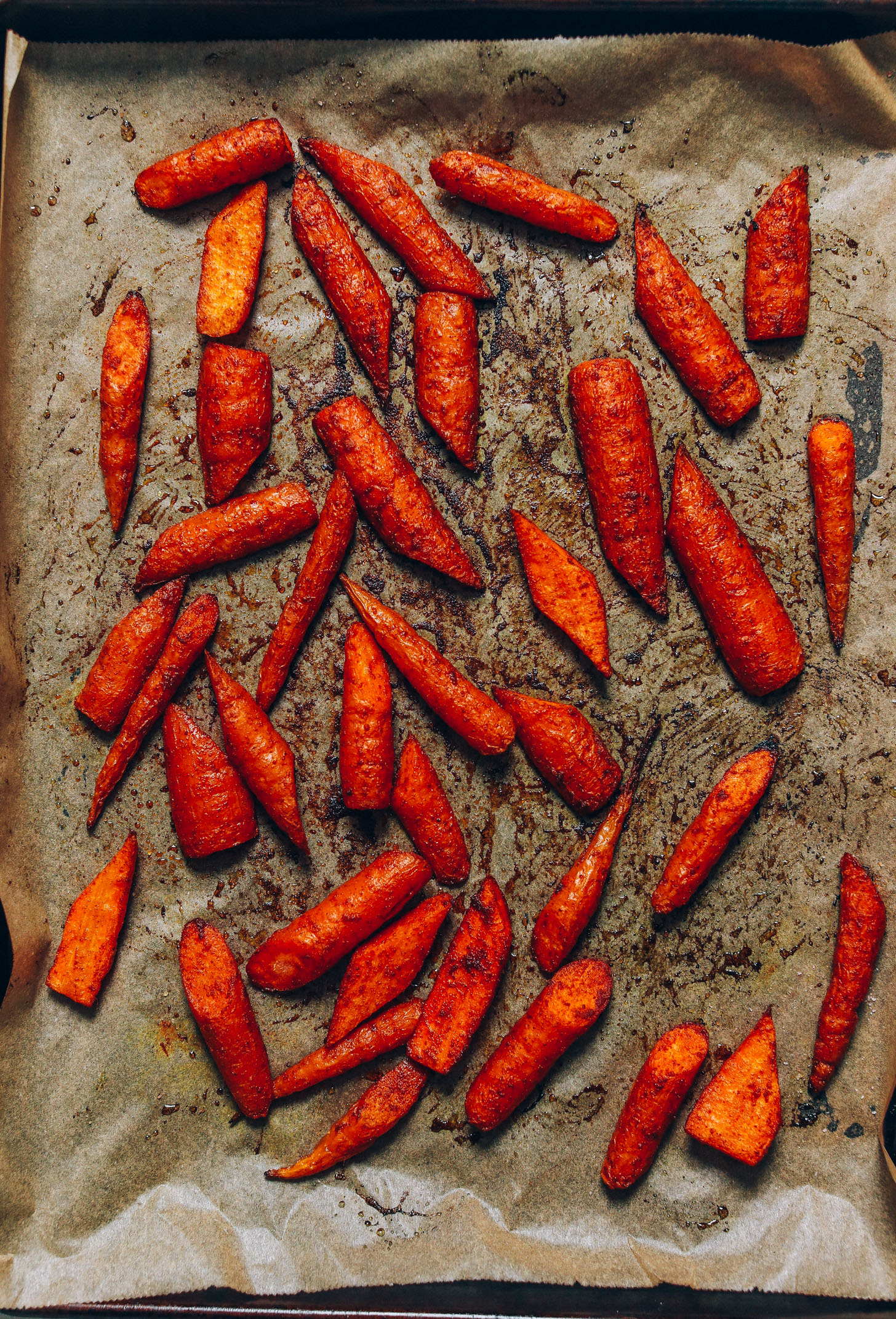 Perfectly roasted carrots on a parchment-lined baking sheet