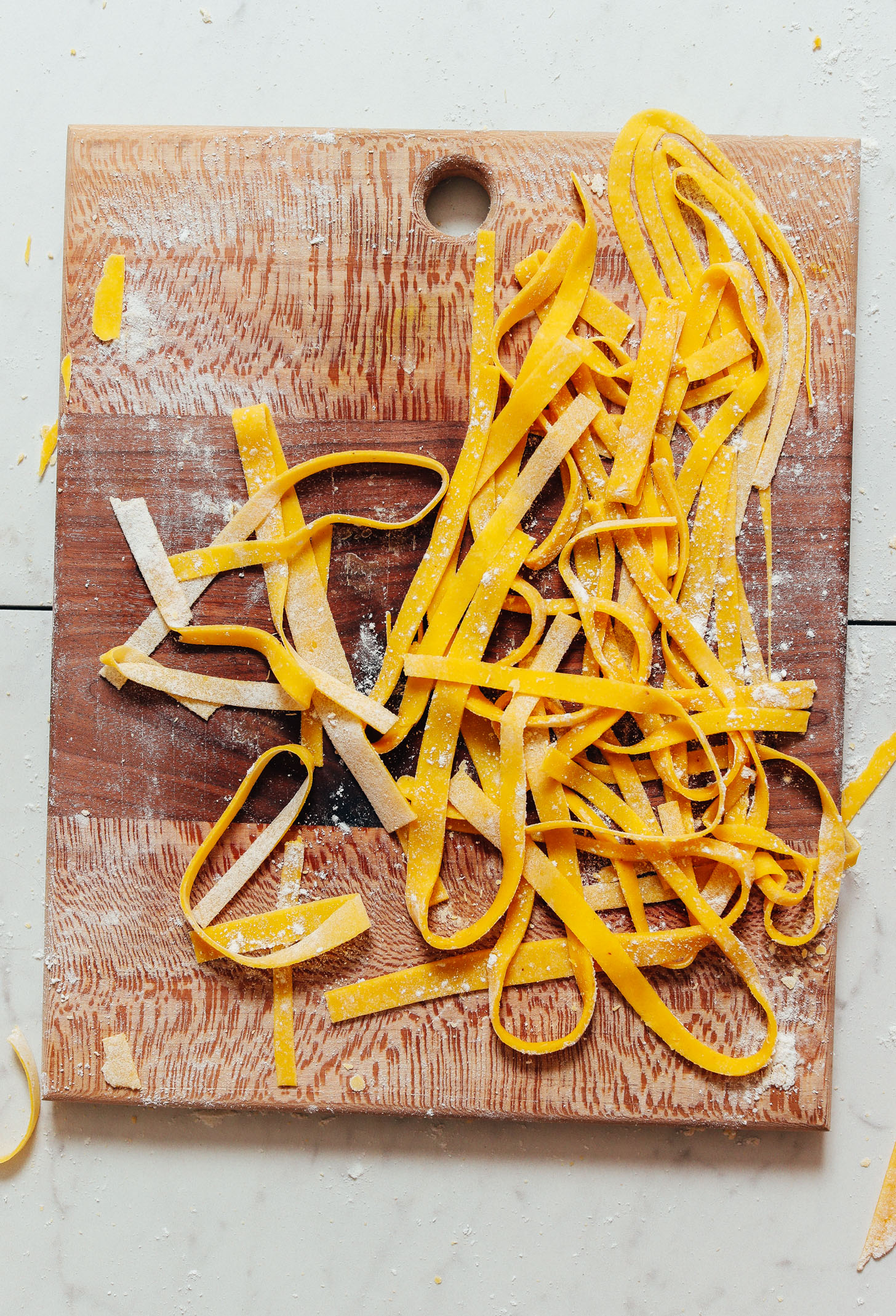 Cutting board of homemade Gluten Free Egg Noodles before cooking