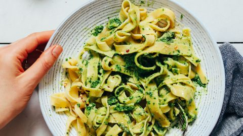 Using a fork to twirl a plate of homemade Gluten-Free Pasta topped with pesto