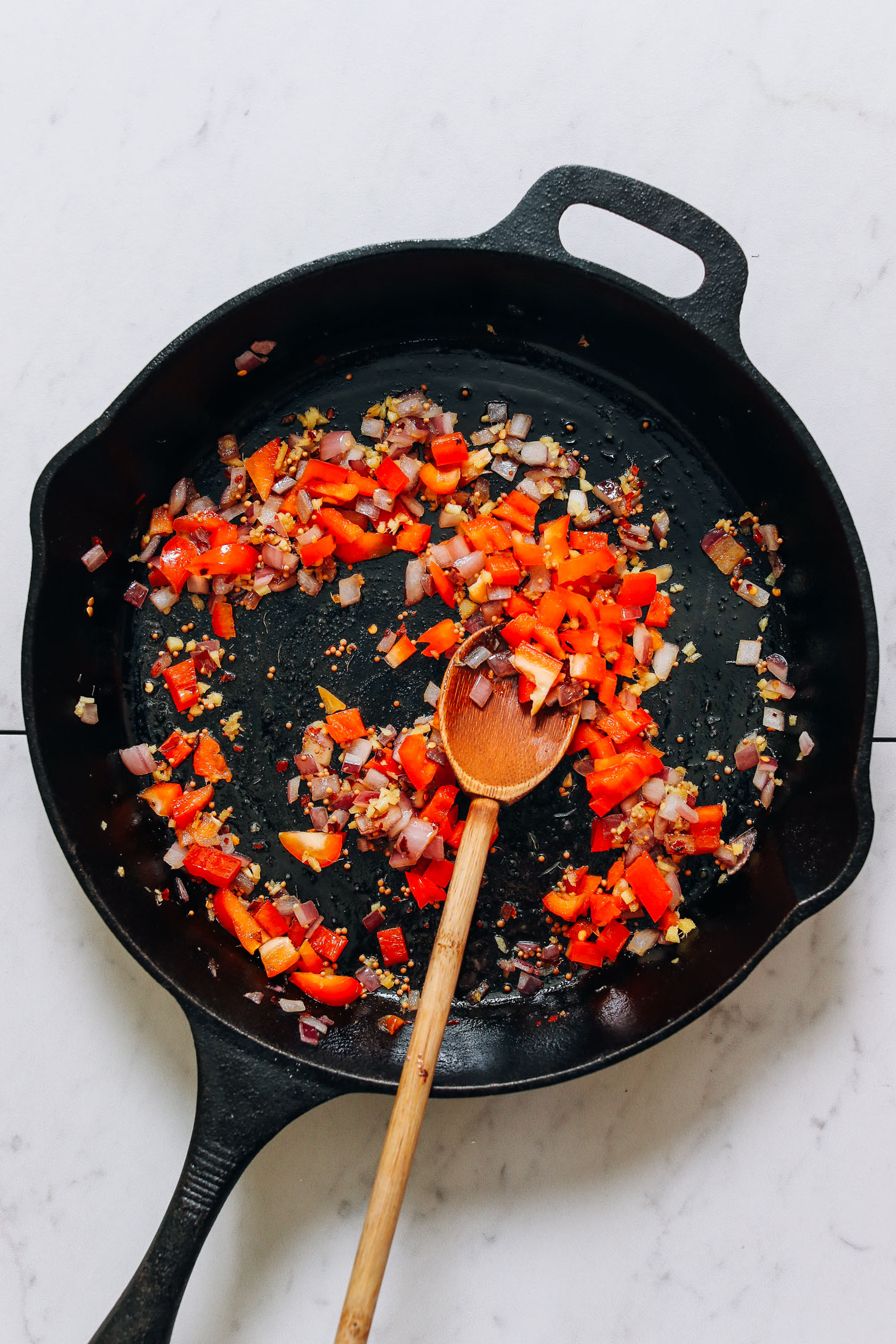 Sautéed onion, bell pepper, and spices in a cast iron skillet for making our Potato Aloo Sabzi recipe