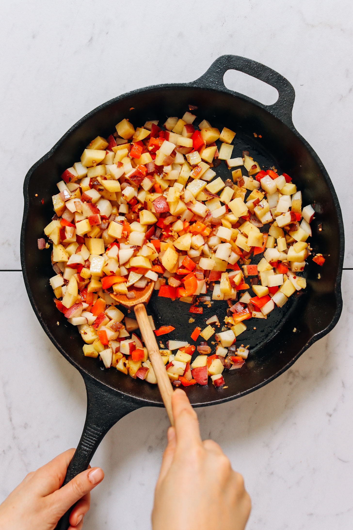 Using a wooden spoon to stir ingredients for Potato Aloo Sabzi in a cast-iron skillet