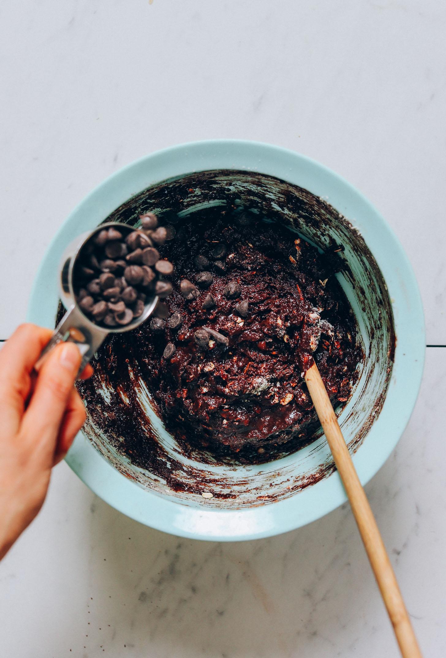 Verter chips de chocolate en un tazón de masa de muffin de chocolate y plátano