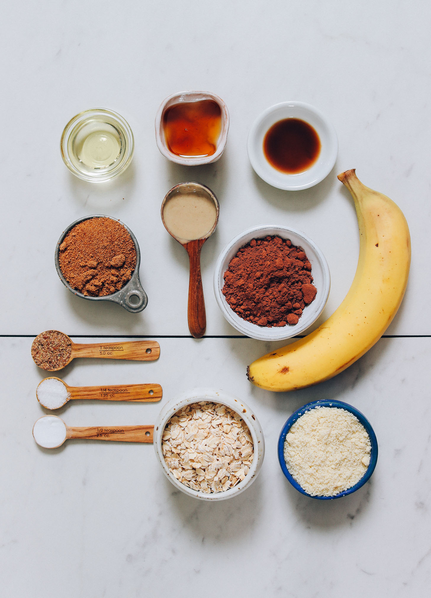 Banana, almond flour, oats, cocoa powder, coconut sugar, maple syrup, and other ingredients for making Banana Chocolate Muffins