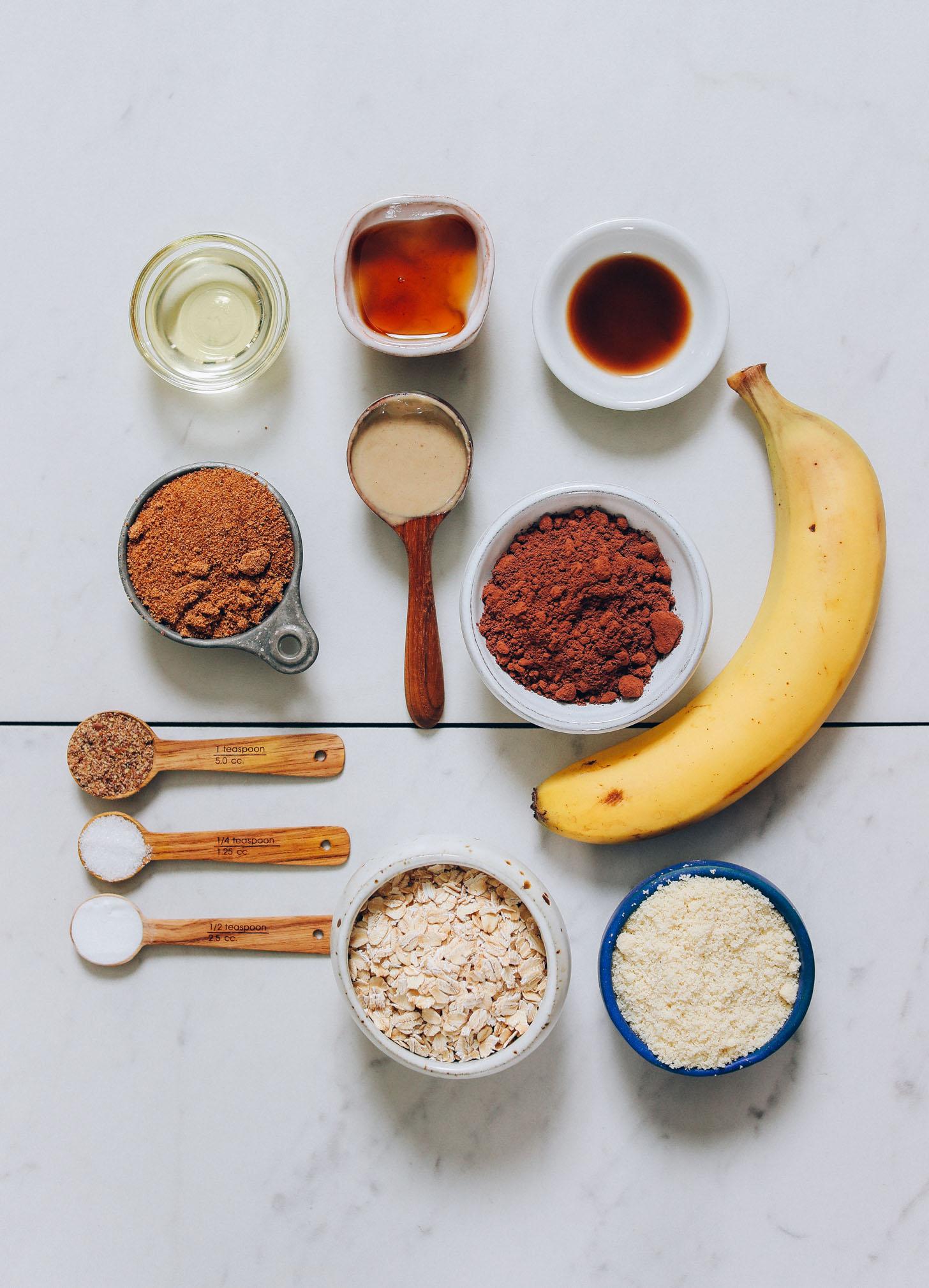 Plátano, harina de almendras, avena, cacao en polvo, azúcar de coco, jarabe de arce y otros ingredientes para hacer muffins de chocolate y plátano