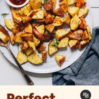Large plate of our Perfect Roasted Potatoes recipe beside a bowl of ketchup