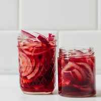 Two jars of Quick Pickled Onions on a white tile background