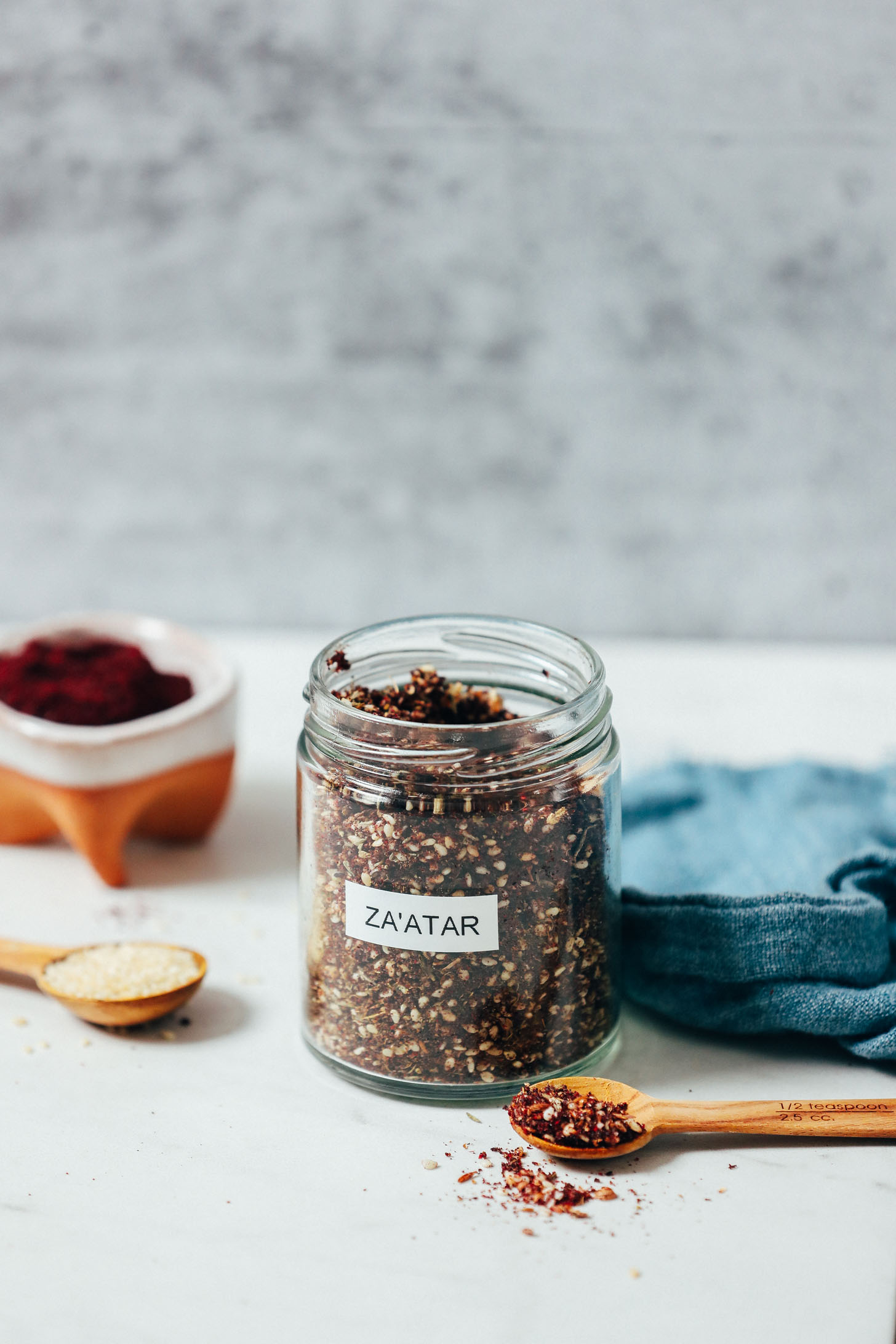 Spoonful and jar of za'atar seasoning next to sesame seeds and sumac