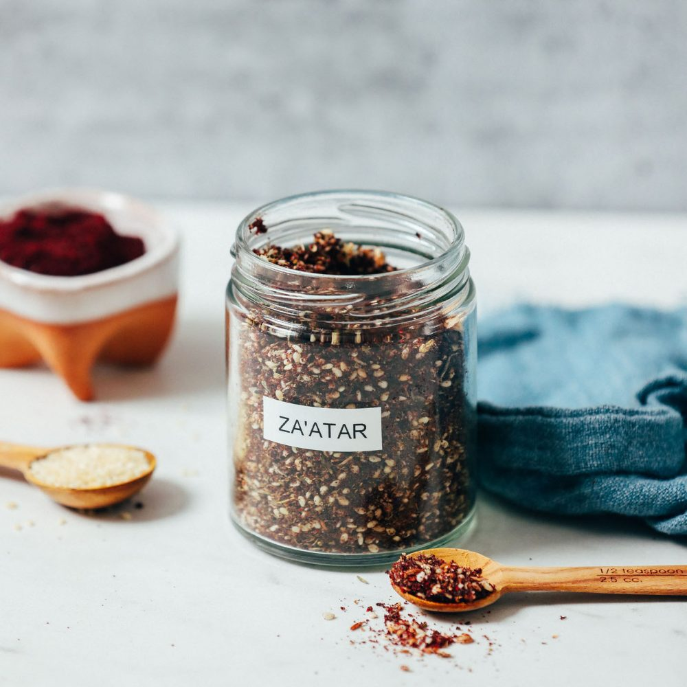 Spoonfuls of sesame seeds and za'atar next to a jar