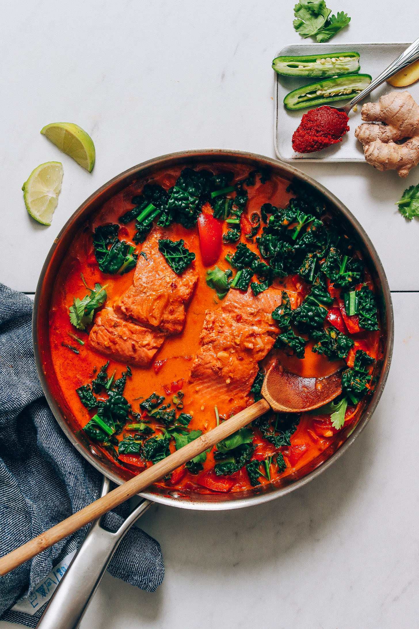Wooden spoon resting in a pan of our 1-Pan Salmon Red Curry recipe