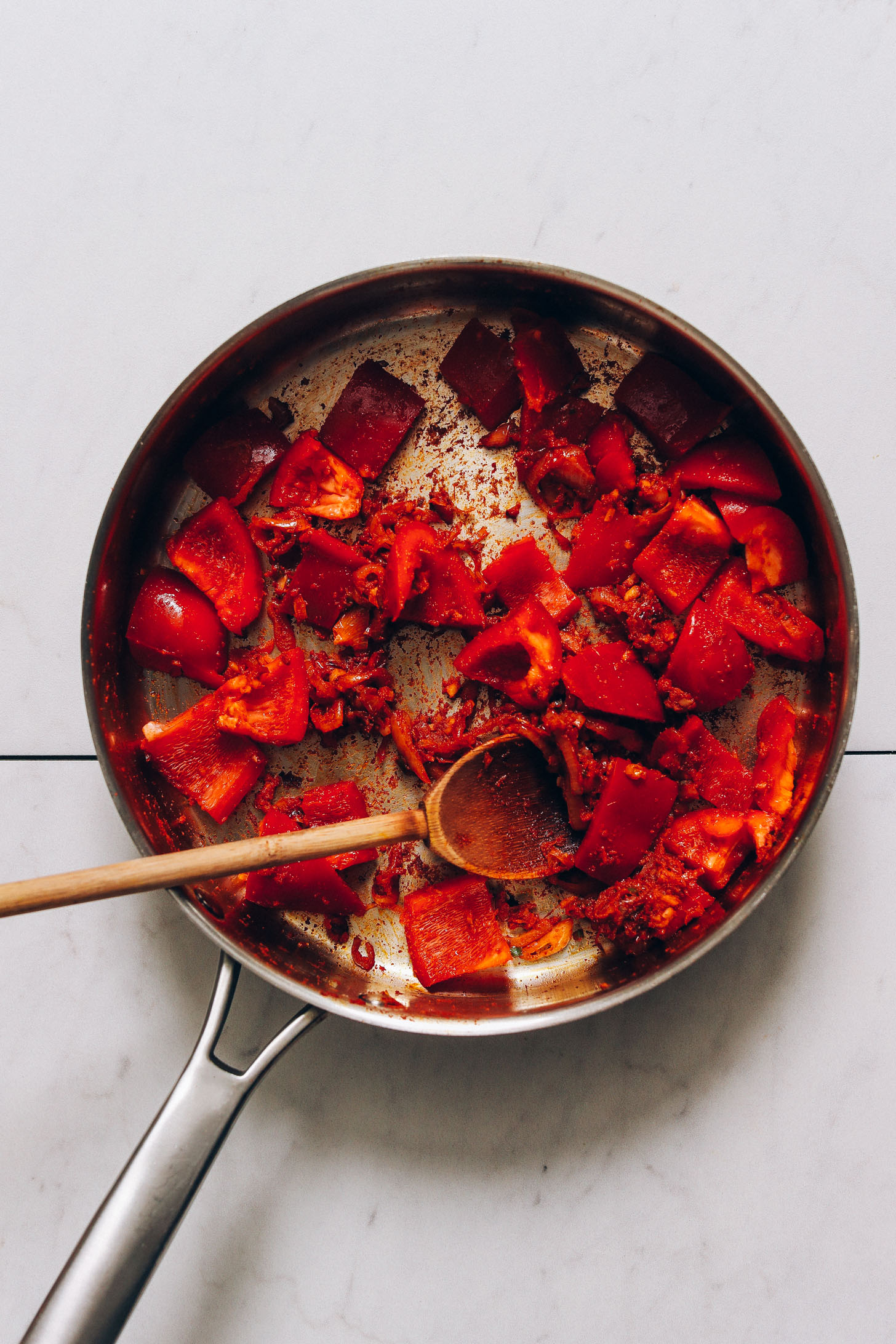 Skillet of sliced bell pepper, shallot, red curry paste, and other ingredients