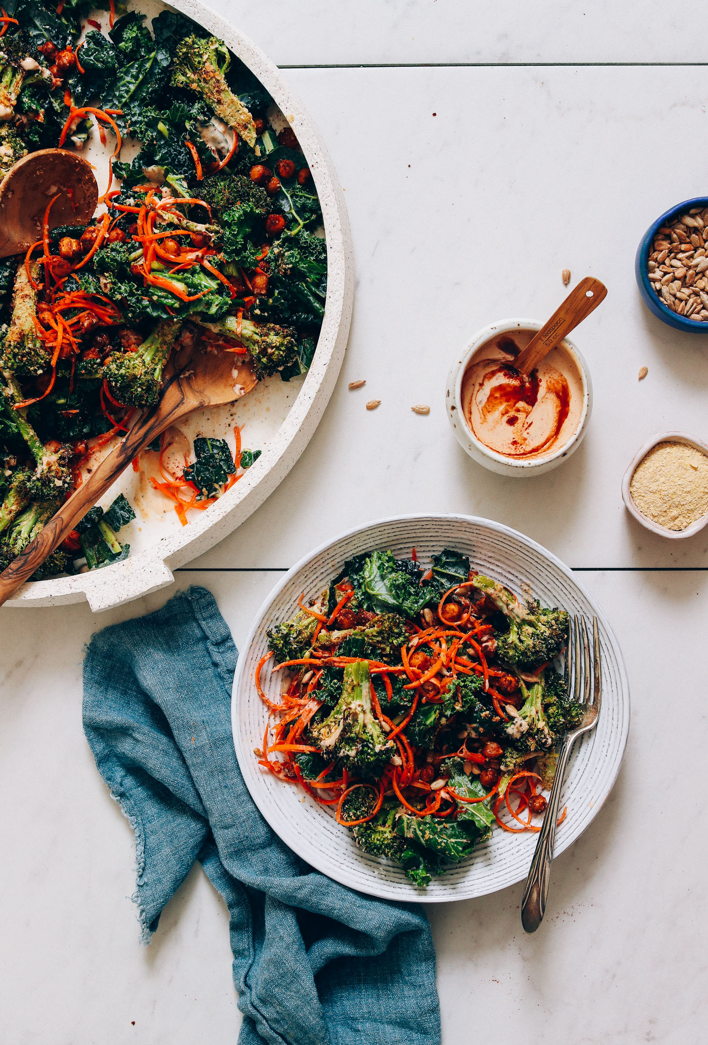 Bowl and platter of Cheesy Roasted Broccoli & Chickpea Kale Salad beside a bowl of Smoky Chipotle Dressing