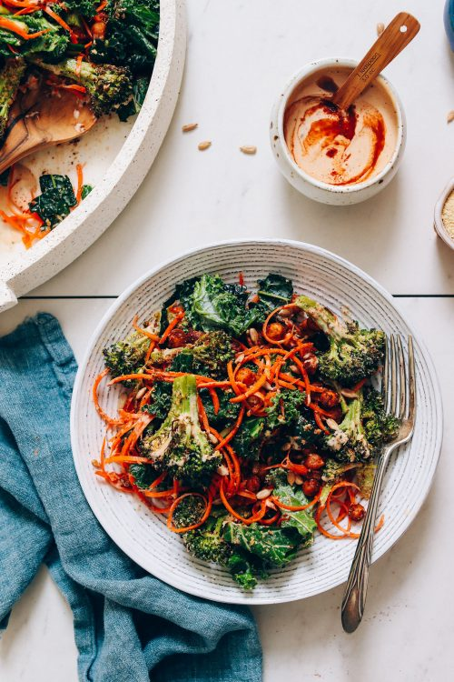 Bowl of smoky chipotle dressing beside a plate and platter of chickpea kale salad