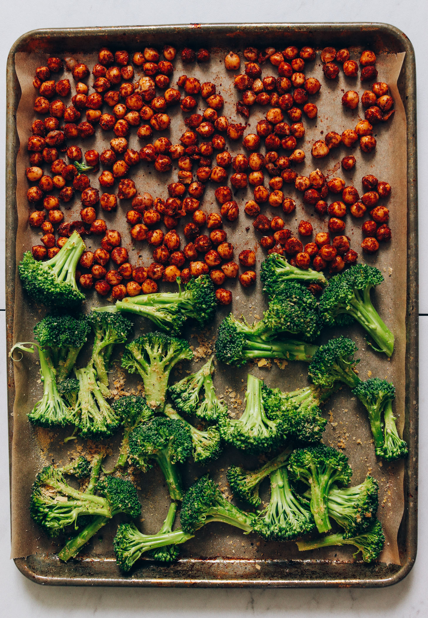 Parchment-lined baking sheet of broccoli and seasoned chickpeas