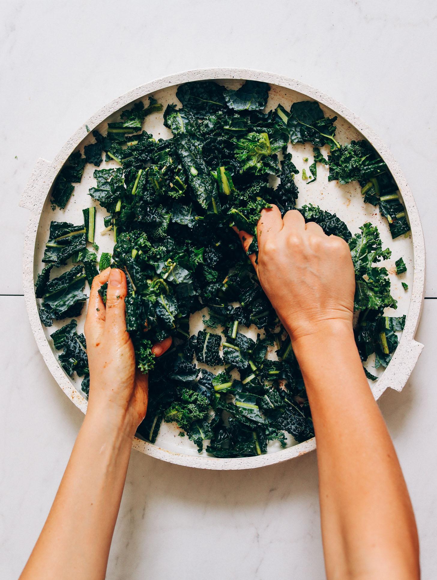 Massaging lacinato kale on a platter