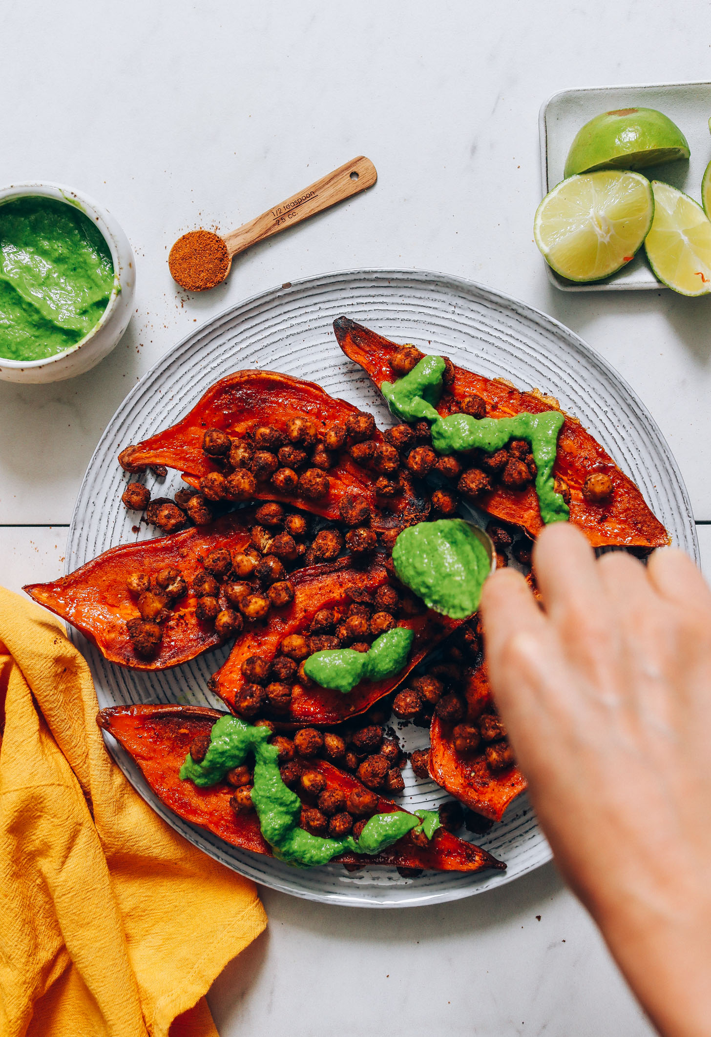 Drizzling green chutney onto a plate of stuffed sweet potatoes