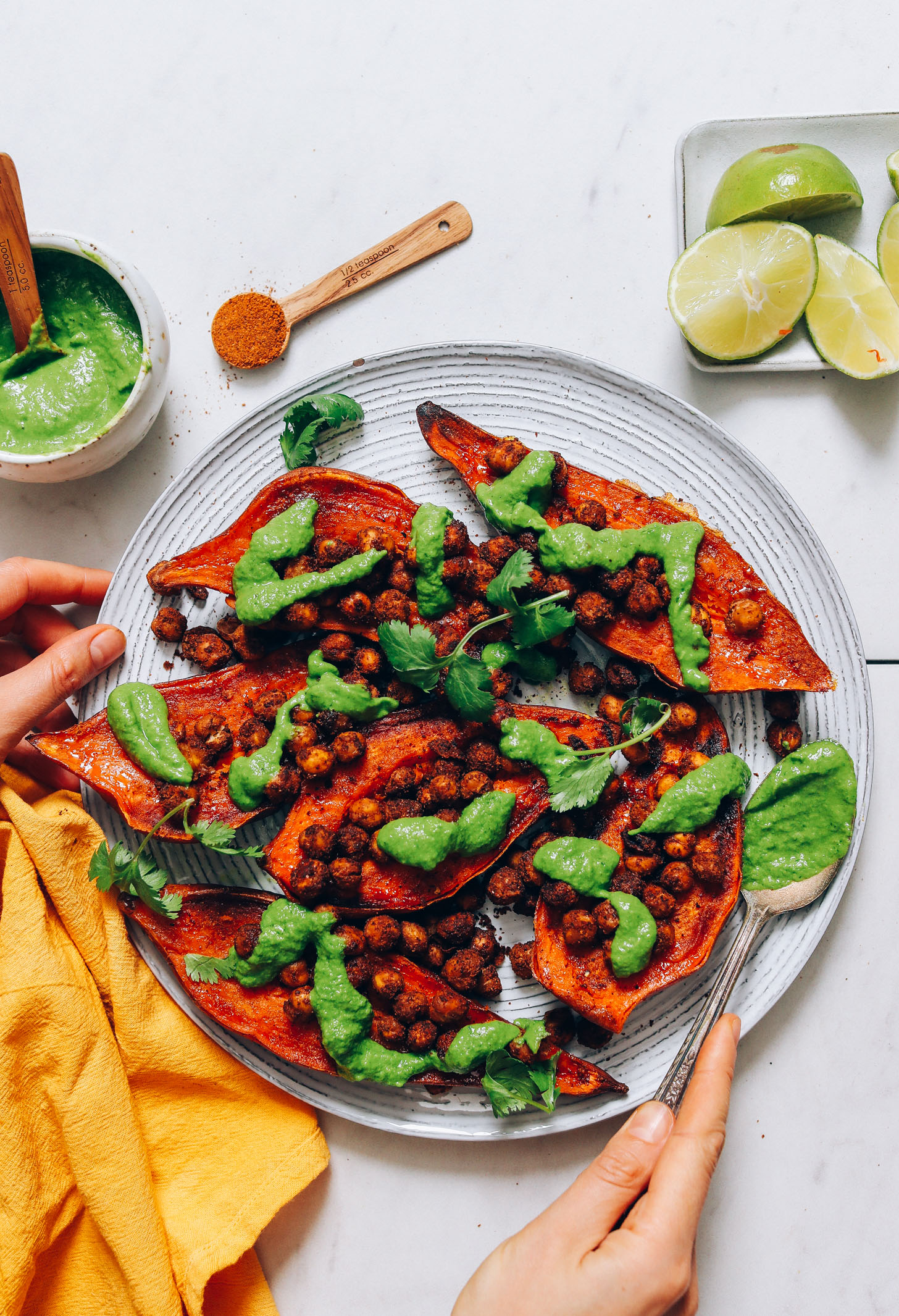 Plate of vegan Masala Chickpea Stuffed Sweet Potatoes with green chutney