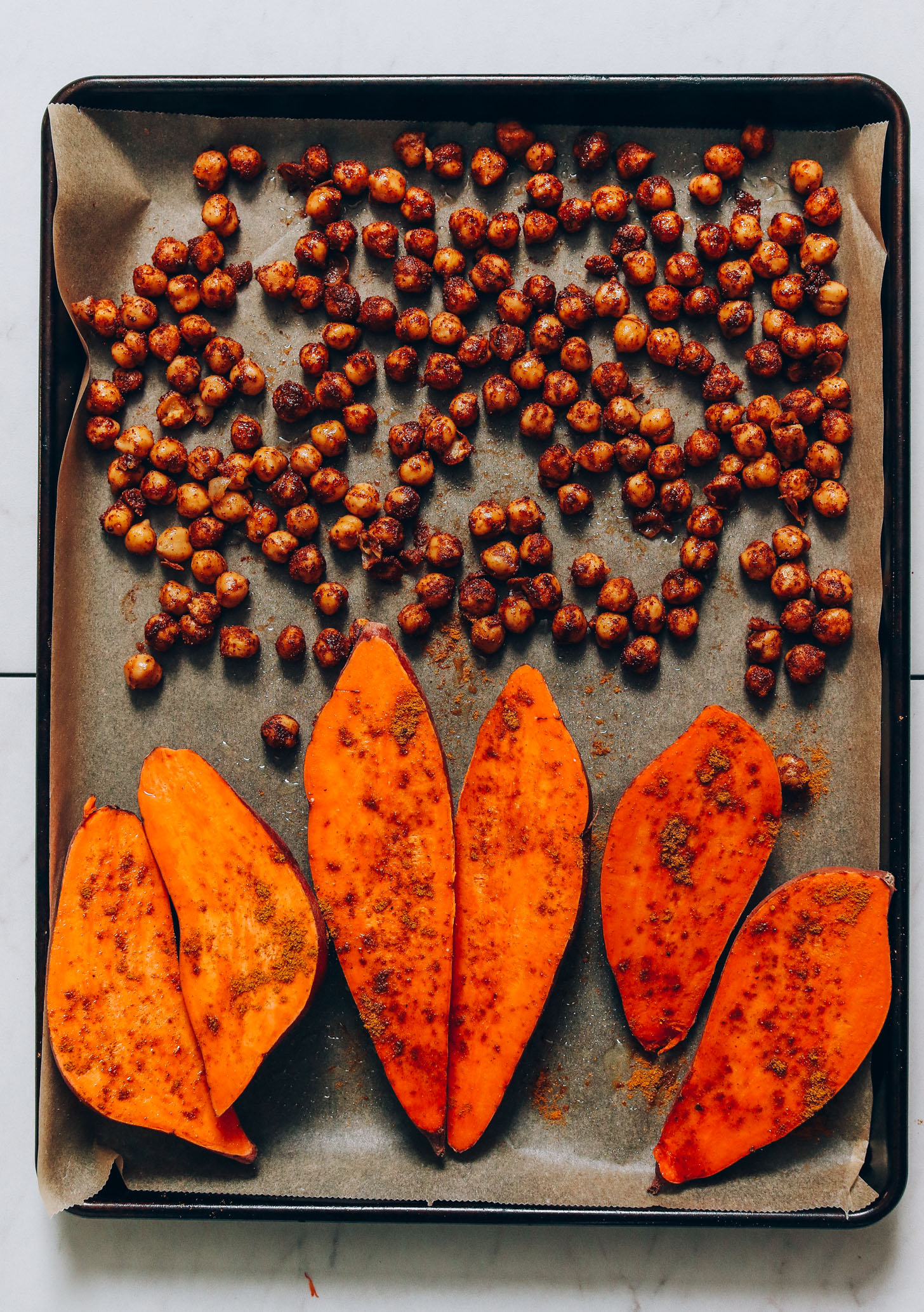 Parchment-lined baking sheet of sweet potatoes and chickpeas topped with tandoori masala seasoning