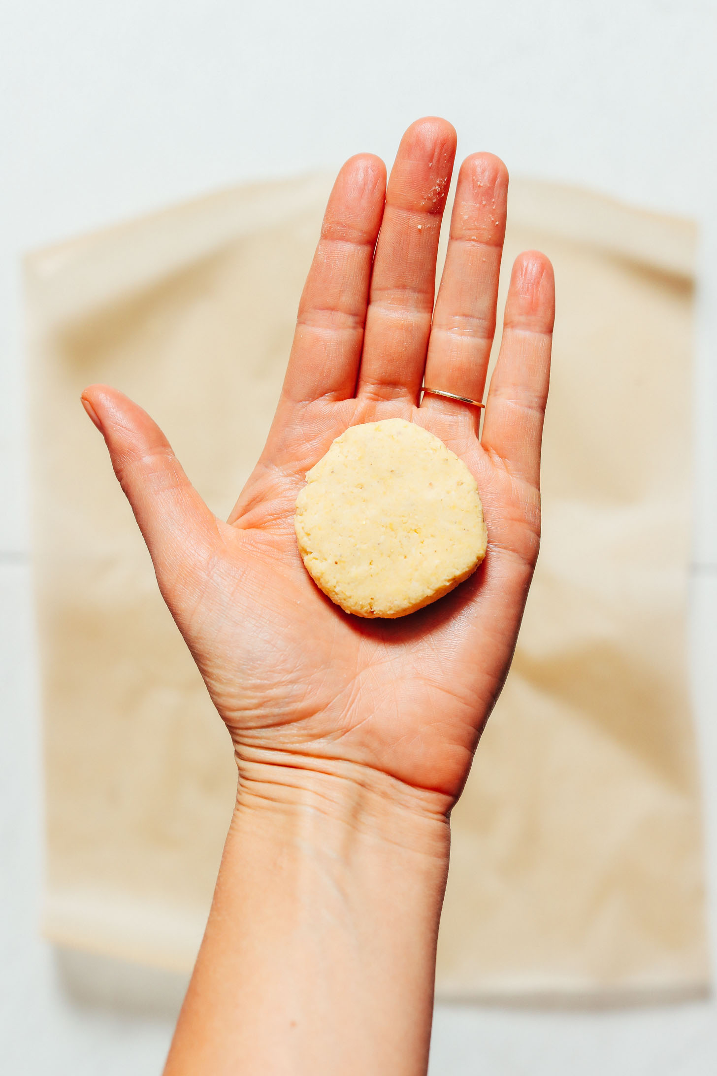 Holding a circle of corn tortilla dough for our tutorial on How to Make Tortillas