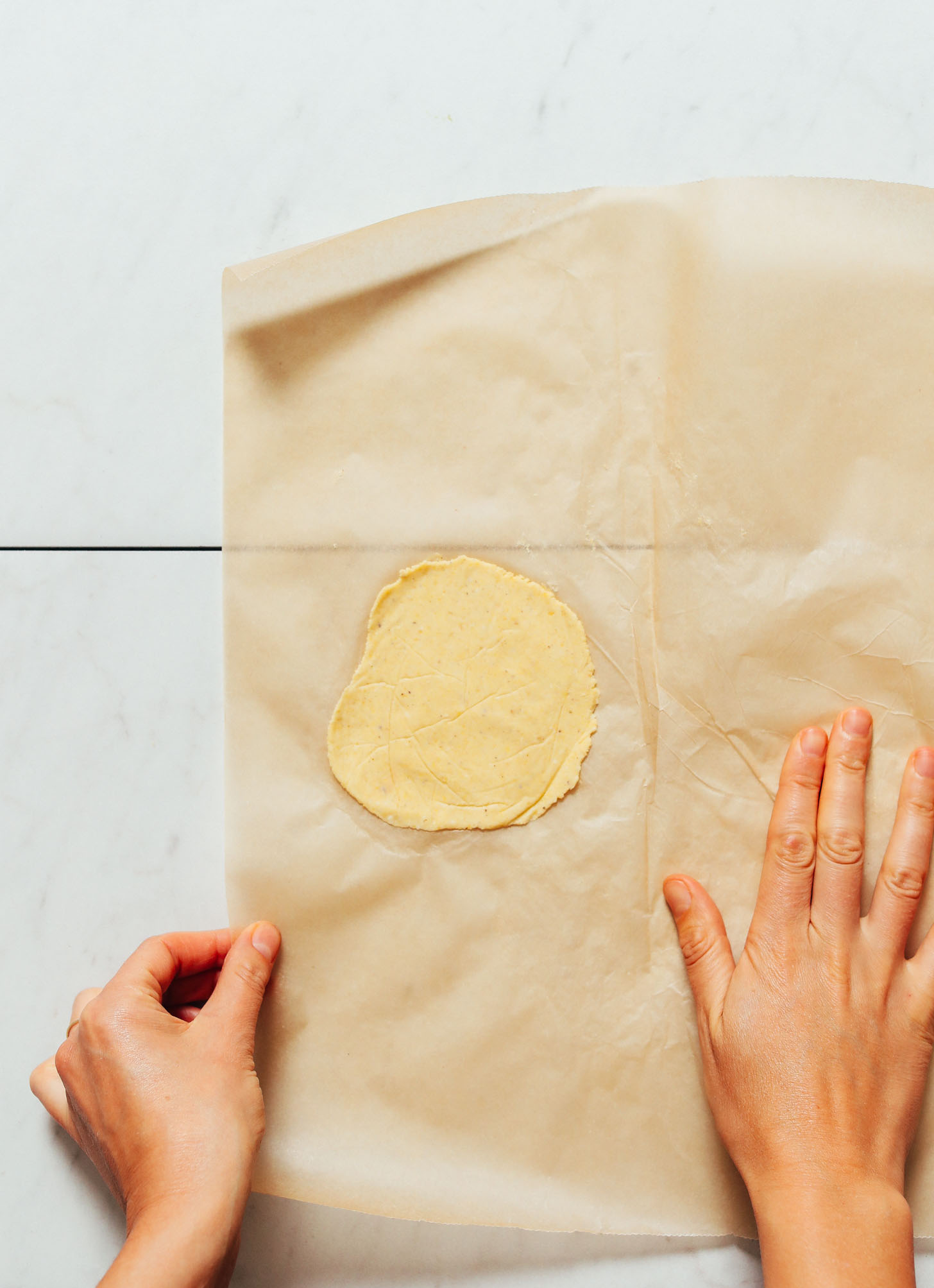 Corn tortilla on a piece of parchment paper for our tutorial on How to Make Tortillas