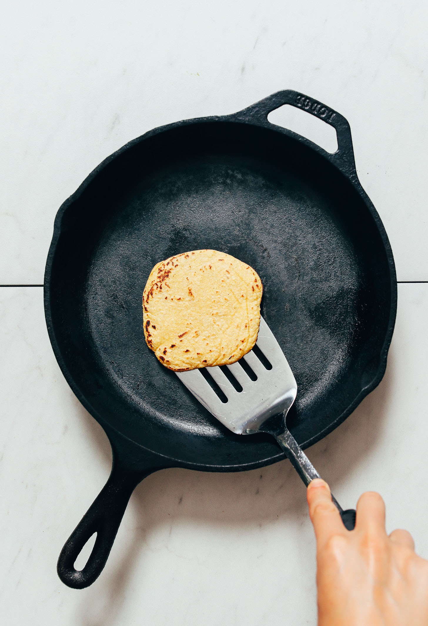 Using a metal spatula to flip a homemade corn tortilla