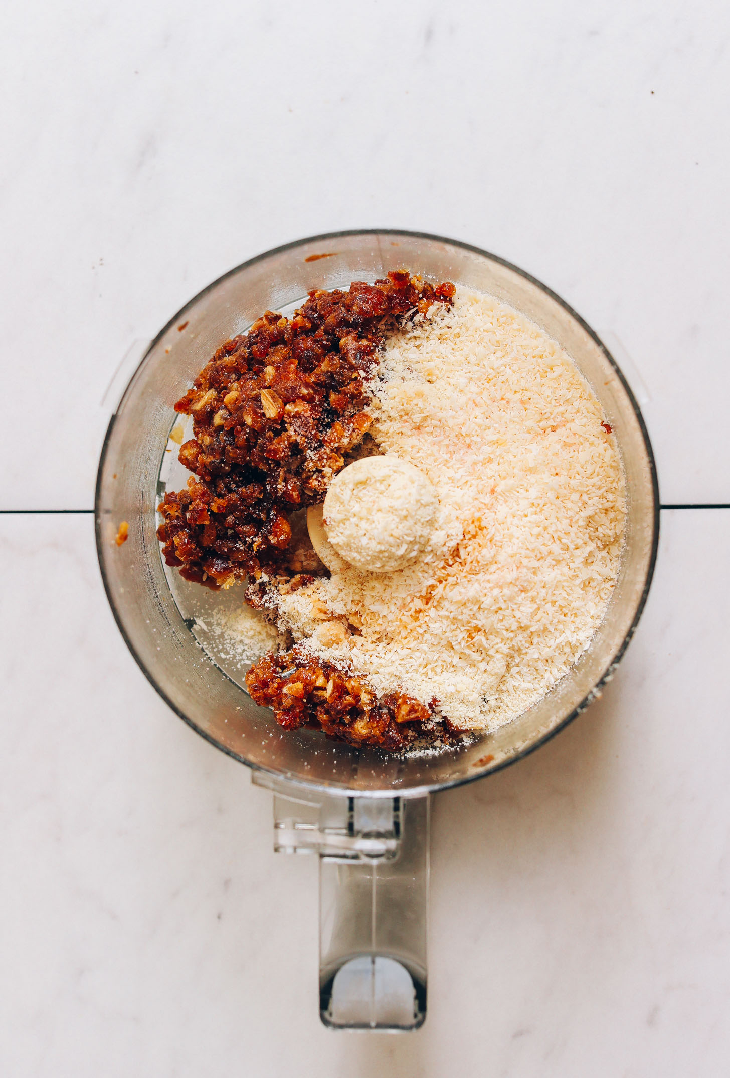 Food processor of almond flour, desiccated coconut, and chopped pitted dates