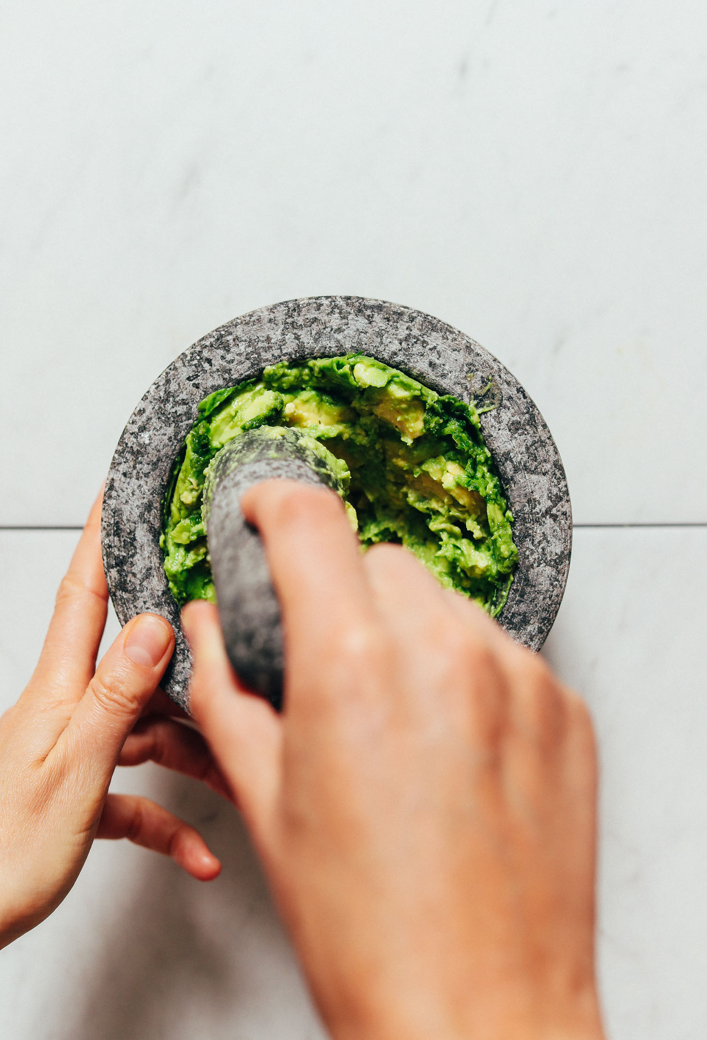 Using a mortar and pestle to smash avocado for making guacamole