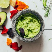 Chip in a mortar and pestle of Serrano & Rosemary Guacamole